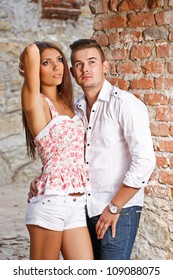 Young couple against a brick wall.