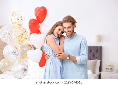 Young couple with air balloons in bedroom. Celebration of Saint Valentine's Day