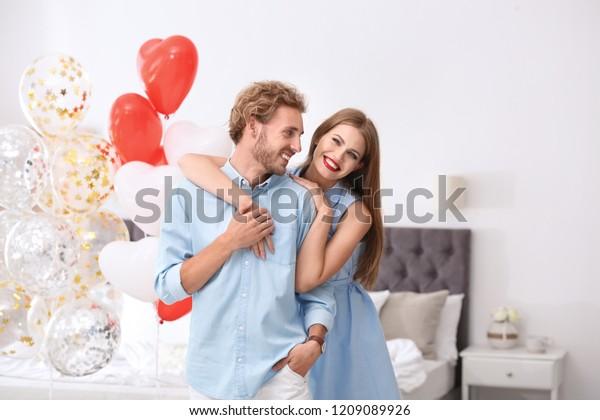 寝室に風船を持つ若い夫婦。バレンタインデーのお祝い