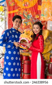 Young couple in ao dai dresses holding a mask of lion