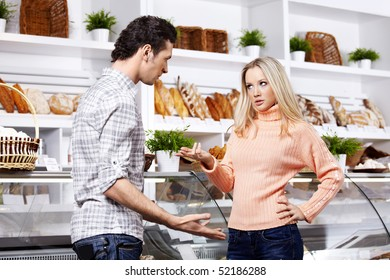 The young couple argues in grocery shop