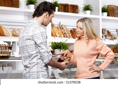 The young couple argues at a shop show-window