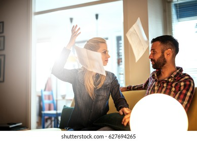 Young couple arguing about financial problems at home. Woman is throwing papers in the air while her husband is upset.
