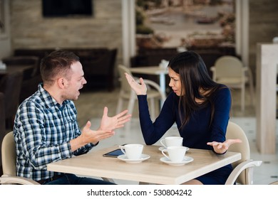 Young couple arguing in a cafe. She's had enough, boyfriend is apologizing. Relationship problems.