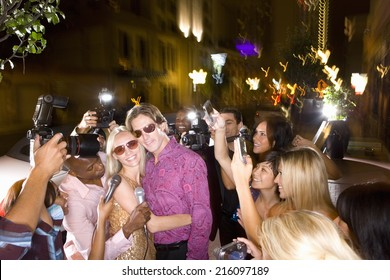 Young couple arm in arm surrounded in paparazzi, smiling