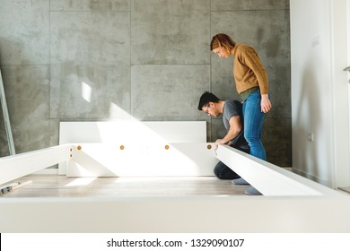 Young couple assembling the bed