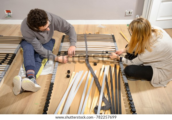 Young couple assembling new bed in a new house