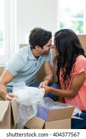 Young couple assisting each other while unpacking carton boxes in new house