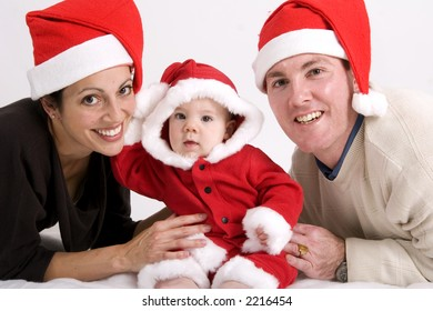 Young couple with baby dressed in Santa hats