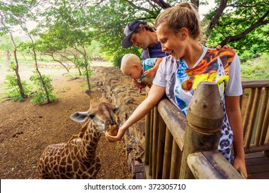 young couple with a baby feeding a giraffe at the zoo on a jungle background. The child laughs. Mauritius Casela Safari Park