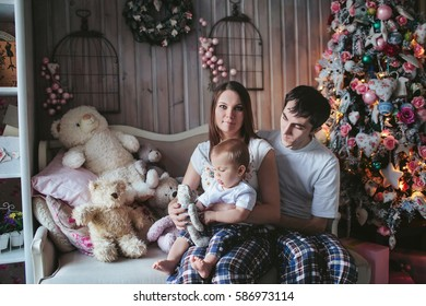 young couple with a baby in pajamas celebrate new year