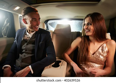 Young couple in the back of a limo looking at each other