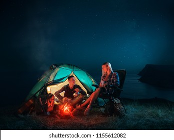Young couple backpackers enjoying in the camping at night near the campfire. Romantic family Campsite. Happy man and woman hiking in the mountains.