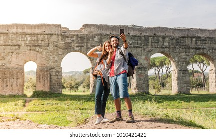 Young couple backpackers tourists with guitar taking selfies in front of roman aqueduct ruins in acquedotti park in rome.