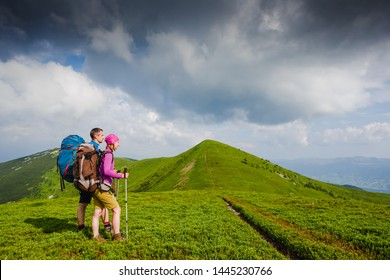 Young couple with backpacks hiking in the mountains and enjoying valley view