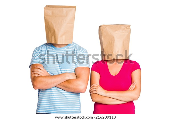 Young couple with bags over heads on white background