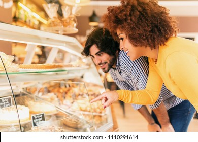Young couple at bakery, looking at the showcase to eat something. They feel happy.