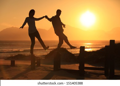 Young couple balancing on some pillars at sunset on the beach.