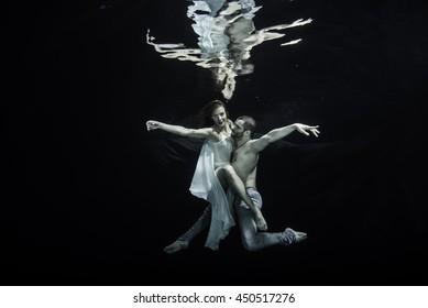 Young couple of ballet dancers dancing underwater