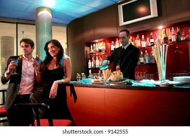 A young couple at bar with cocktails