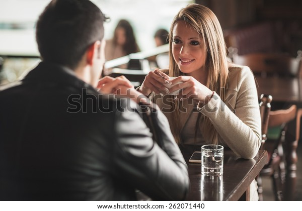 Young couple at the bar having a coffee and flirting