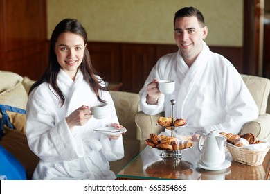 Young couple in bathrobes having coffee with buns in hotel room