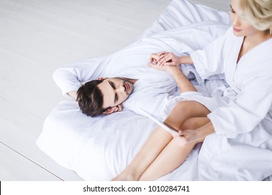 young couple in bathrobes holding hands while girl using digital tablet on bed