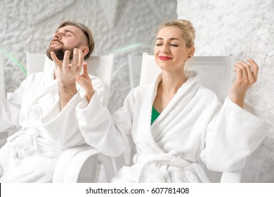 Young couple in bathrobes meditating in the salt room