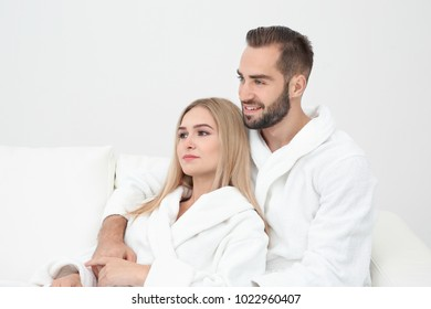 Young couple in bathrobes relaxing on sofa 6d0e23904