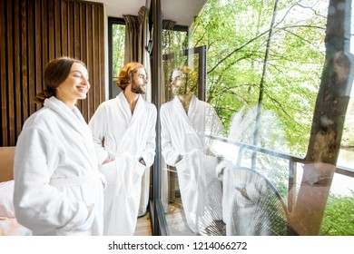 Young couple in bathrobes standing near the window with beautiful view on the forest at the modern hotel room