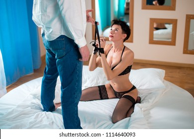 Young couple in bdsm action a bed in hotel room