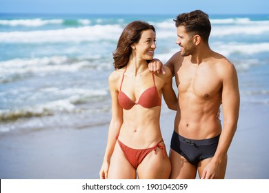 Young couple of beautiful athletic bodies walking together on the beach enjoying their holiday at sea