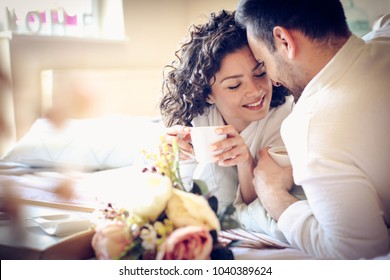 Young couple in bed drinking coffee.