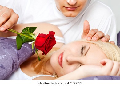 young couple in bed, male is waking female with rose