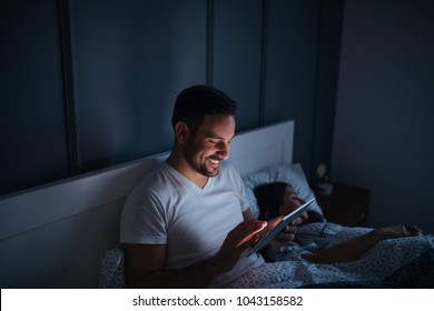 Young couple in the bedroom at night. Man using his tablet.