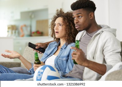 young couple with beer watching tv at home