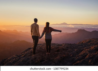 young couple from behind holding hands while standing on mountain top with scenic landscape and sunset in the background