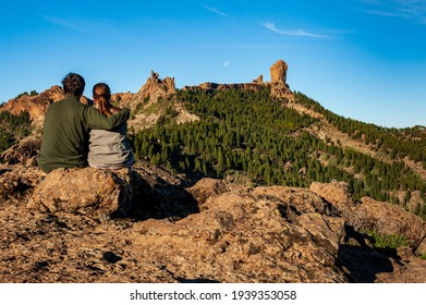 Young couple from behind sitting and watching Roque Nublo, symbolic natural monument of Gran Canaria. Summer sunny day blue skies and moon. Emblematic volcanic rock formations Canary Islands Spain.