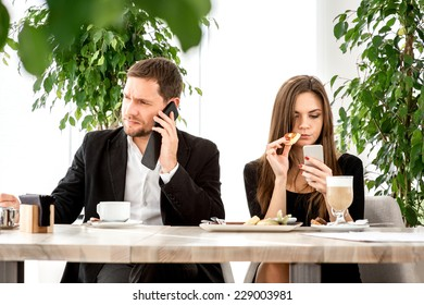 Young couple being busy using their smart phones at the restaurant