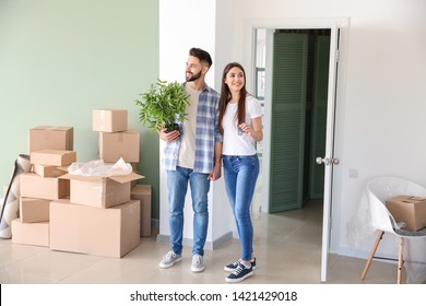 Young couple with belongings in their new house