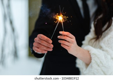 Young couple with Bengali lights in winter forest. Hands with Bengali lights. Happy festive couple with lit sparklers celebrating Christmas outdoors. People, winter, holidays, the concept of outdoors