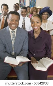Young couple with Bibles sitting on church pews, portrait