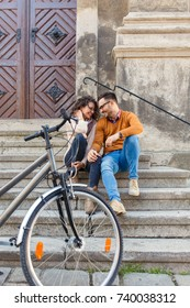 Young couple with bicycle siting on stairs in the city.