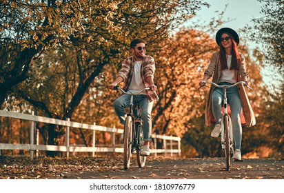 Young couple with bicycles in park in autumn time.  - Shutterstock ID 1810976779