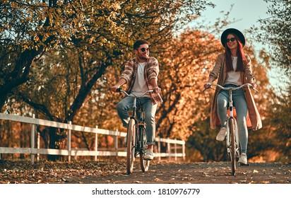 Junge Paare mit Fahrrädern im Park im Herbst.