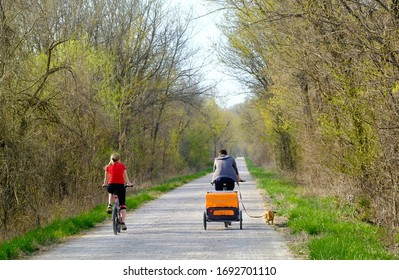 Young couple bicycling on trail in park on a nice spring day in Midwest; man has a baby trailer behind his bicycle and small dog on leash