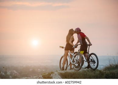 Young couple bikers kissing on the top of a hill on bicycles against beautiful sunset. Blurring background. Copy space