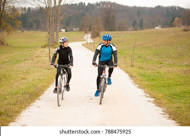 Young couple biking on an autumn afternoon in nature