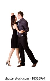 young couple in black attire dancing happily