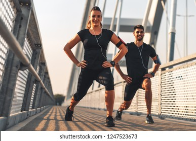 Young couple in black sports outfit doing morning workout outdoors. Young man and woman stretching they muscle before running on bridge.